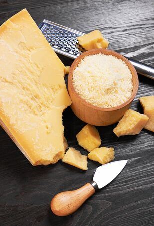 Parmesan cheese on wooden board with grater and knife