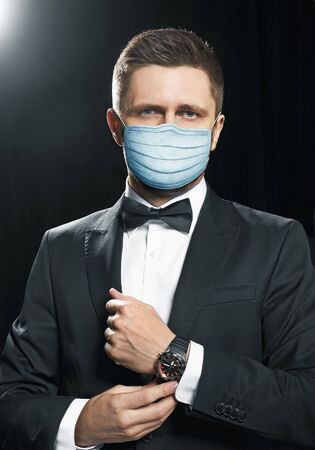 Man in black suite in a protection mask, for a prevention from covid-19 virus