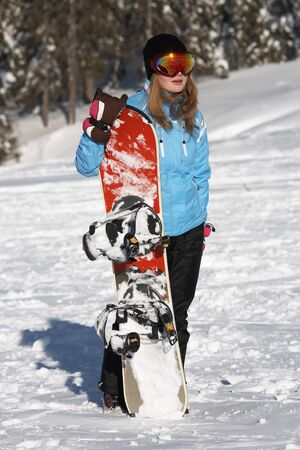Young woman snowboarder with snowboard Standard-Bild