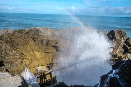 blowhole pancake rock with rainbow at punakaiki
