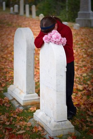 A young girl weeps at a grave