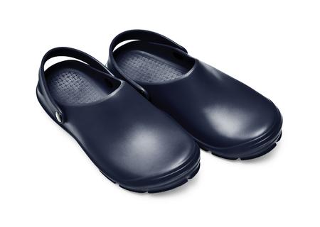 Crocs-schoenen. Een paar zwarte belemmeringen die op witte achtergrond met weg worden geïsoleerd