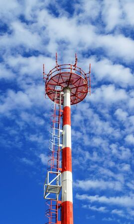 Telecom tower for wireless transmission of radio, cell phone or internet signal. Telecom mast painted in red and white color with blue sky and clouds in the background