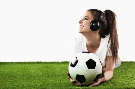 earbud: Portrait of a handsome girl holding a football on white background