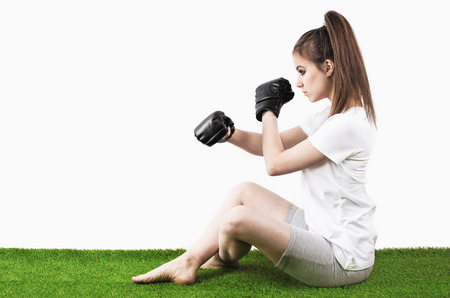 Boxing girl on the green grass. White background