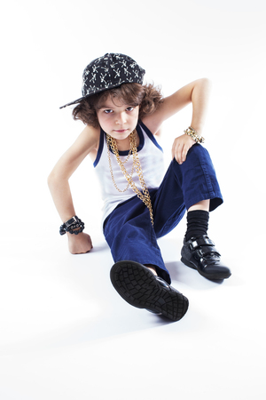 Little curly rapper in a baseball cap sitting on the floor and looking into the camera. White background.