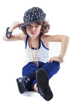 rapping: Funny Kinky rapper sitting on the floor holding his hand over the visor baseball cap looking at the camera. White background. Stock Photo