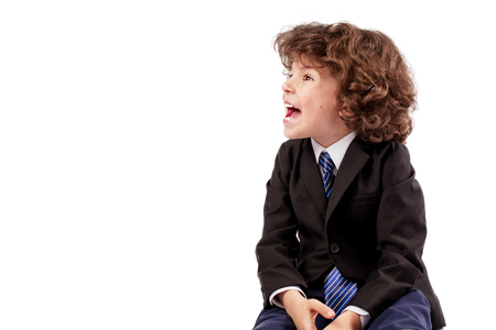 Curly boy in a jacket and tie is looking to the right and shouts. White background.