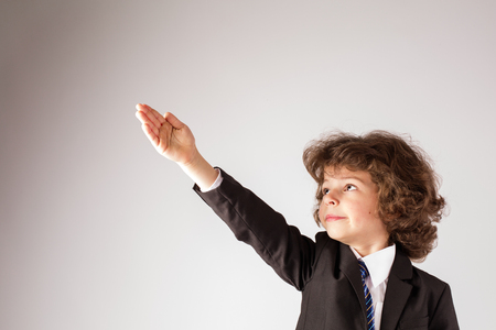 Funny curly boy raised his hand up. Gray background. Imagens