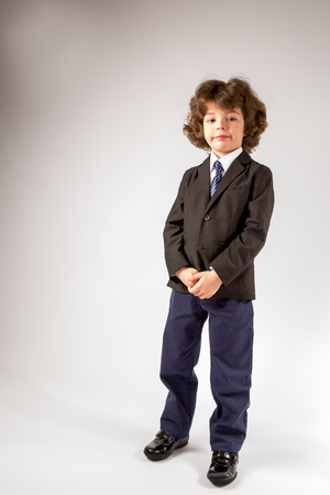Cute boy standing and looking at the camera in a business suit. Grey background. Imagens