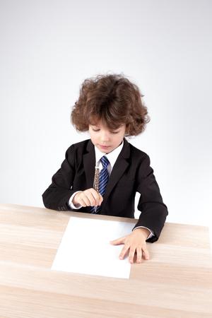 El pequeño jefe de pelo rizado pensó en el contrato. Fondo gris De cerca. Foto de archivo