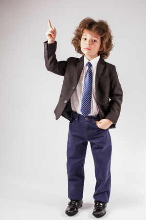 Curly cute boy in a business suit holding up a hand gesturing and looking at the camera. Gray background. Imagens