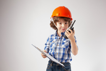 Little curly-haired foreman with a clipboard in his hand talking on the radio. Gray background. Stock Photo