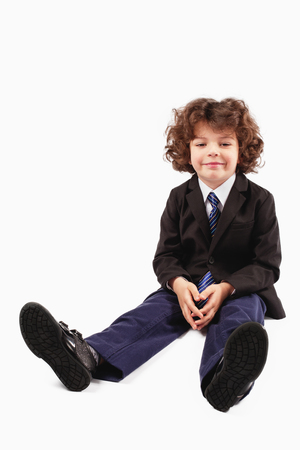 Little curly boy in a business suit sitting on the floor with legs stretched and looking at the camera. White background. Imagens