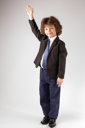 Funny curly boy raised his hand in a business suit, smiling and looking at the camera. Full length. Gray background.