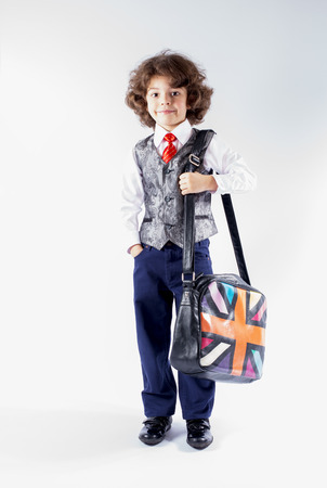 Funny curly-haired boy in waistcoat goes to school with a bag over his shoulder. Gray background. Stock Photo