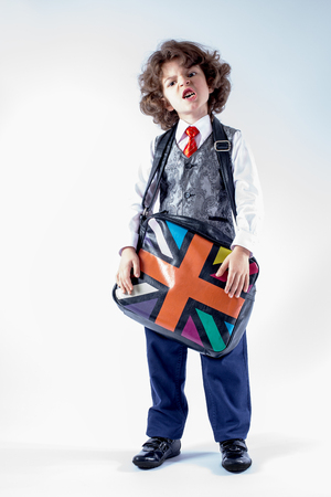 Funny curly-haired boy in waistcoat holding a bag over his shoulder, his head bowed. Gray background. Stock Photo