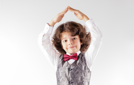 Curly cute boy in waistcoat and bow tie, he folded his hands over his head. Close-up. Gray background.