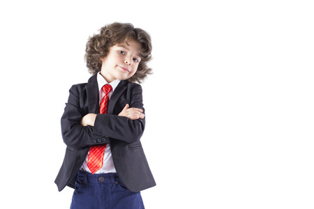 bowing head: Curly cute boy with his arms crossed smiling, bowing his head and looking at the camera. White background. Stock Photo