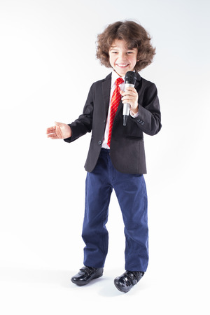 Little curly-haired boy with a microphone in her hand is smiling and looking at the camera. Full length. Gray background.