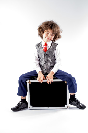 Cute curly little boy sitting on the black suitcase and looking into the camera. Gray background. Stock Photo