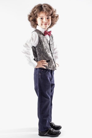 Cute curly boy stands sideways to the camera, and turning his head looking at the camera. Full length. White background.