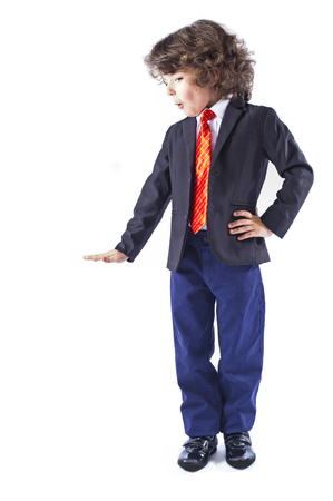 Cute curly-haired boy in a business suit stands and pats an imaginary dog. Full length. White background.