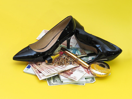 Collage. Jewelry, cash, cosmetics and black female shoes. Yellow background.