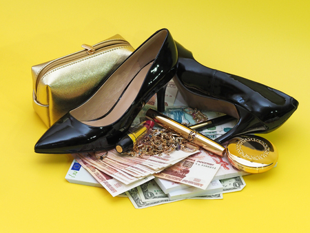 Collage. Cash, bag for cosmetics, jewelry, cosmetics and black womens high heels. Yellow background.
