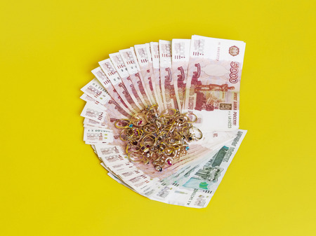 Jewelry are on banknotes. Yellow background.