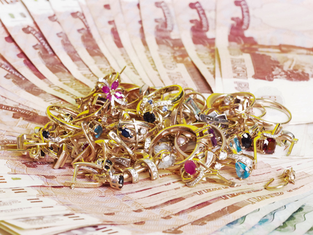 Gold jewelry with sapphires, rubies, emeralds are on the banknotes. Stock Photo