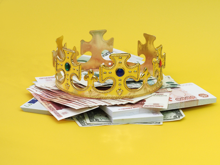 The royal crown with precious stones lying on a stack of banknotes. Yellow background.