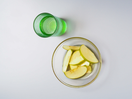 Sliced green apple lies in a plate with honey. It is worth a glass of water. View from above. Imagens