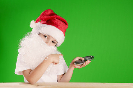 Little Santa Claus looking at the camera head bowed. One hand shows on a green background, in the other hand holding a remote control. Remote is aimed at green background. ?hromakey. Close-up.