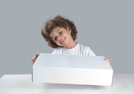 Cute curly little boy sitting at the table head cocked, holding a white box. He looks into the camera. Gray background. Close-up. Reklamní fotografie