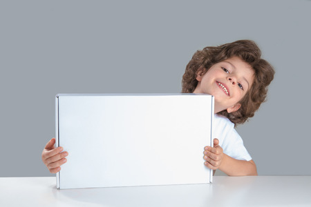 Cute curly little boy sitting at a table holding a white box. He looks into the camera. Gray background. Close-up.