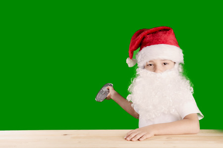 A little boy in an image of Santa Claus looking at the camera. Remote control in his hand. Finger presses the button. The control unit is aimed at green background. ?hromakey. Close-up.