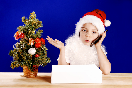persuade: Little Santa Claus emotionally talking on a smartphone. Gift in a white box on the table. Blue background. Close-up.