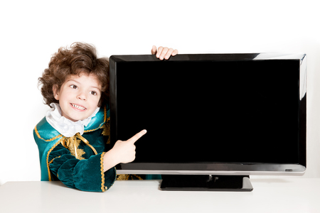 Cute curly Prince points to the blank screen TVs. White background.