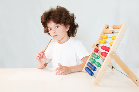 abaco: Cute curly-haired boy with pencil in hand looks thoughtfully into the camera. Close-up. Gray background.