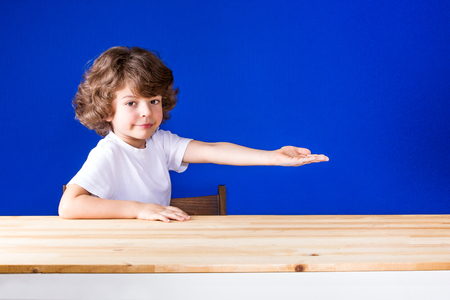 Funny curly cute boy sitting half-turned his hand outstretched and smiling looking at the camera. Close-up. Blue background.