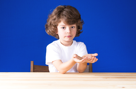 Curly cute boy with folded hands in the boat looking into the camera. Blue background. Stock Photo