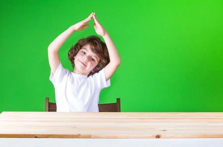 Curly cute boy holding his hands above his head house, smiling and looking at the camera. Close-up. Green background.