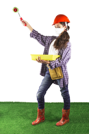 A beautiful girl in a face mask and helmet stands with a paint roller. White background. Green grass floor.