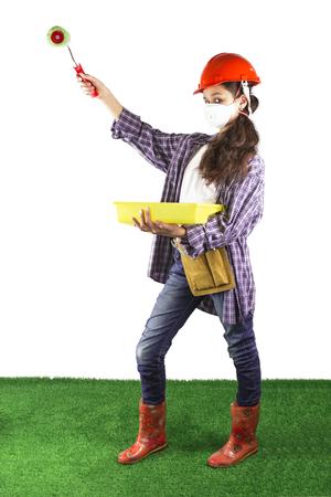 Een mooi meisje in een gezichtsmasker en helm bevindt zich met een verfrol. Witte achtergrond. Groene grasvloer. Stockfoto