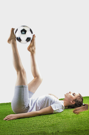Pretty womens soccer. Young brown-haired woman in sportswear lies with a soccer ball on the grass , isolated on gray background