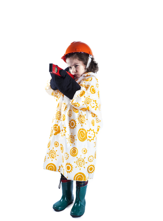 Cute curly-haired boy builder in a raincoat holing a building level. Foreman in an orange construction helmet and construction gloves. White background.