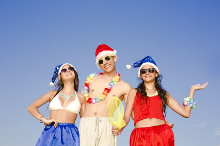 Concept: New Year on the beach. The company - a boy and two girl in clothes for the new year on the beach