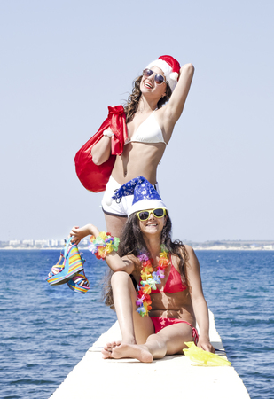 Two girlfriends in santa hat during beach vacation Stock Photo