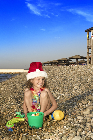 Little boy in Santa hat with toys on the beach